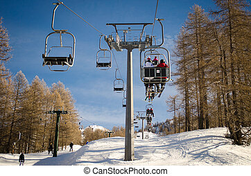 Aerial lift (chairlift) and skilift in sunny day - People...