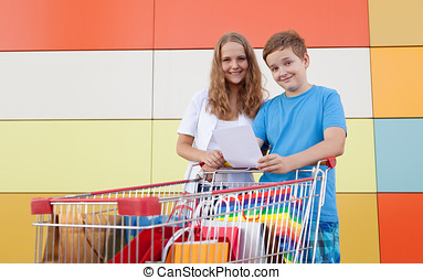 Young buyers - boy and girl with shopping trolley full of...