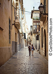 Loving couple walking down the street in Palma de Mallorca,...