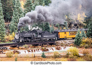 Mountain Train - An antique steam engine locomotive carries...