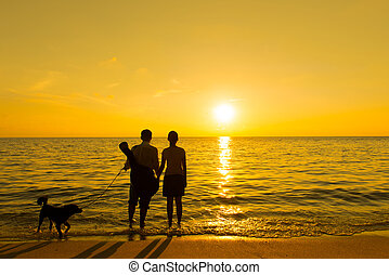 Silhouette of a couple and dog at beach during sunset