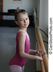 Ballet girl standing next to the ba - A young ballet girl...