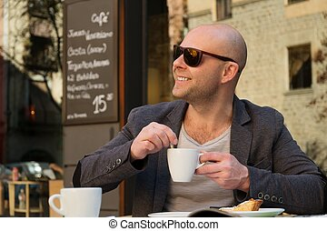 Cheerful middle-aged man with coffee cup in street cafe