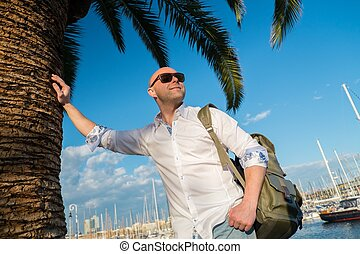 Happy middle-aged man with backpack standing near palm tree...