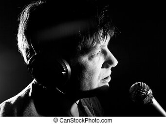 Young male star singer singing into microphone black and...