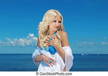 Portrait of beautiful blond woman on blue sky background