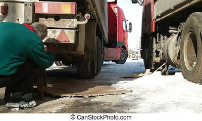 Repairing truck in winter - Truck driver repair his truck in...