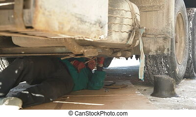 Repairing truck on winter road - Truck driver is working...