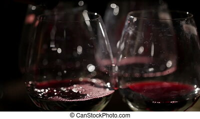 Red wine is poured in the glasses.