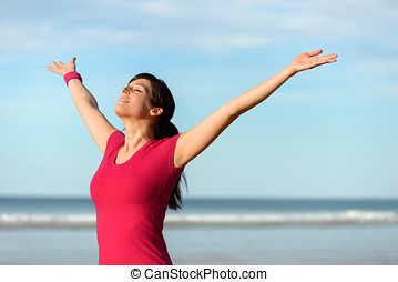 Happy fitness woman raising arms - Blissful fitness woman...