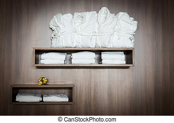 white bathrobes and towels stapled on brown wooden shelf...