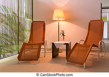 two sunloungers with lamp and table in hotel wellness area