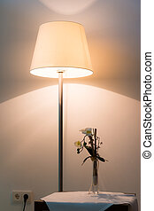 illuminated lamp in front of wall with flower on table