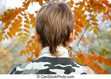 Boy head from back side outdoor over orange leaves