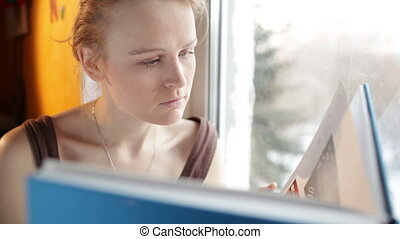 Girl reads a book near window.