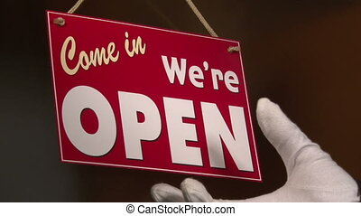 Open Closed sign, close up - Business owner turns sign from...