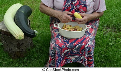 hand peel potato zucchini - senior woman with apron hands...