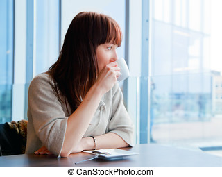 Woman drinking coffee at a corporate restaurant and looking...