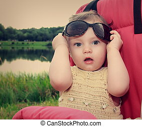 Surprising baby girl holding sunglasses outdoors summer...