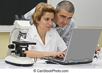 Researchers - Two researchers coleagues analyzing the...