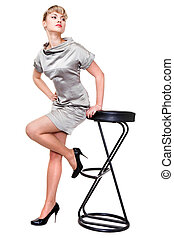 beautiful model in silver dress and black shoes posing on a high chair