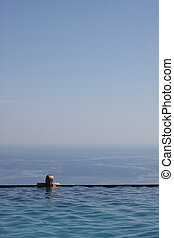 Girl in infinity pool - Girl relaxing at the end of an...