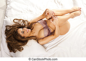 Beautiful happy woman in lingerie lying on her back on a bed...