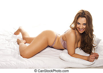 Curvaceous woman in lingerie posing lying on her stomach on...