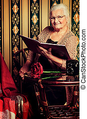storyteller - Portrait of a smiling senior woman reading a...