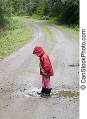 Girl in puddle - A little 4 year old girl is standing in a...