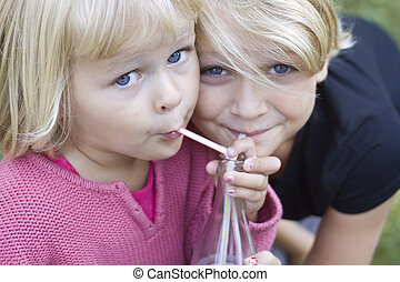 Two young girls sharing - Two blond girls sharing a drink
