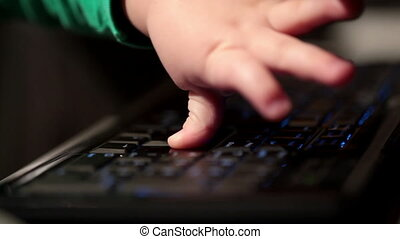Two year old boy is playing with computer. Boy typing on...