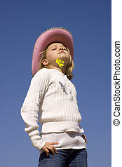 Young girl in sunshine - A young girl with hat and a flower...