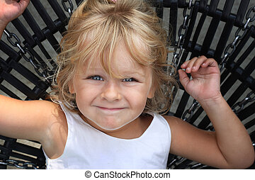 Girl on swing - Little girl lying on a large swing, looking...