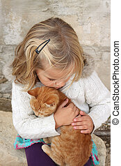 Child with kitten - 5 year old girl holding a cat