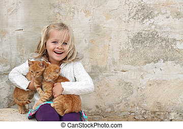 Cute girl holding kittens - A happy girl holding a pair of...