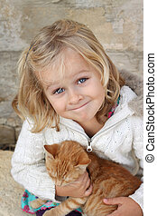 Smiling child with kitten - Cute litte girl holding a cat....
