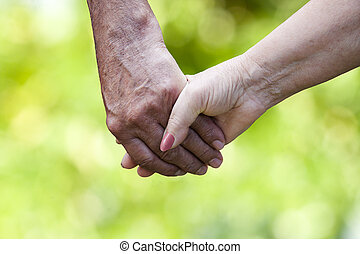 clasped hands of older people with natural background