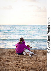 Girl and dog by the ocean
