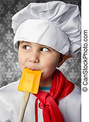 A little boy cook in uniform over vintage  background playing with spoon