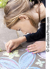 Girl drawing with chalk on pavement - Child drawing with...