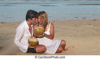 Dating - Attractive happy couple with coconuts have dating...