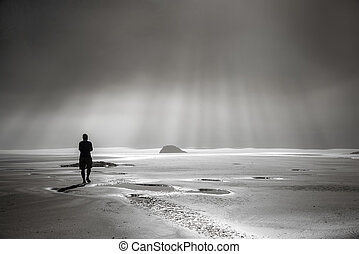 Person walking toward sunbeams - One person walking toward...