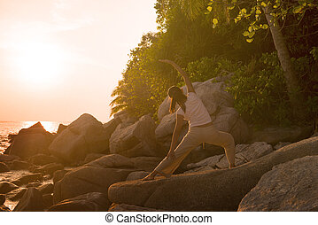 beach yoga , silhouette of a woman performing warrior pose during a beautiful sunset