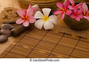 tropical spa setup with frangipani flower hot rocks and...