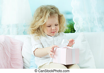 Birthday gift - Adorable child unwrapping a birthday gift at...