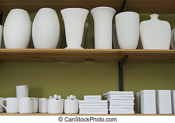 Unfinished Pottery - Unfinished pottery on two shelves.