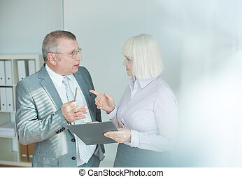 Debates - Confident mature businessman and his colleague...