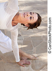 Senior woman doing yoga - A middle aged woman in an advanced...