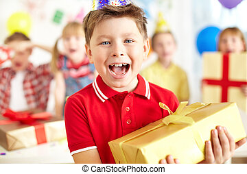 Birthday excitement - Joyful boy with giftbox looking at...